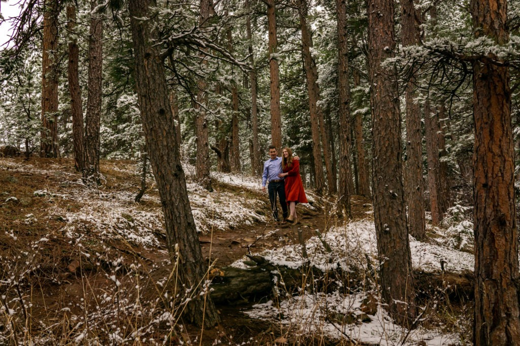 A couple strolling down a wooded trail in a snowy forest during this Boulder engagement session by Gabby Jockers Photography. boulder engagement photography, boulder engagement photos, boulder engagement session, chautauqua park engagement photos, chautauqua park engagement session, chautauqua park photography, Flatirons engagement photos, snowy engagement photos, snowy engagement session, hiking engagement, adventure photos, adventure session, couples photos