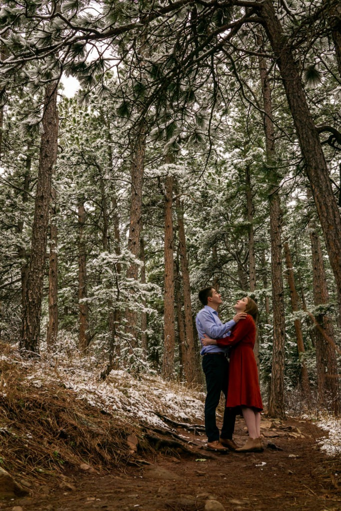 A couple looking up into the sky in a snowy forest during this Boulder engagement session by Gabby Jockers Photography. boulder engagement photography, boulder engagement photos, boulder engagement session, chautauqua park engagement photos, chautauqua park engagement session, chautauqua park photography, Flatirons engagement photos, snowy engagement photos, snowy engagement session, hiking engagement, adventure photos, adventure session, couples photos