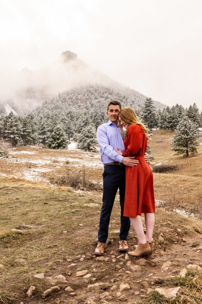 A woman in a red dress snuggling up against her fiance in this Chautauqua Park engagement session by Gabby Jockers Photography. boulder engagement photography, boulder engagement photos, boulder engagement session, chautauqua park engagement photos, chautauqua park engagement session, chautauqua park photography, Flatirons engagement photos, snowy engagement photos, snowy engagement session, hiking engagement, adventure photos, adventure session, couples photos