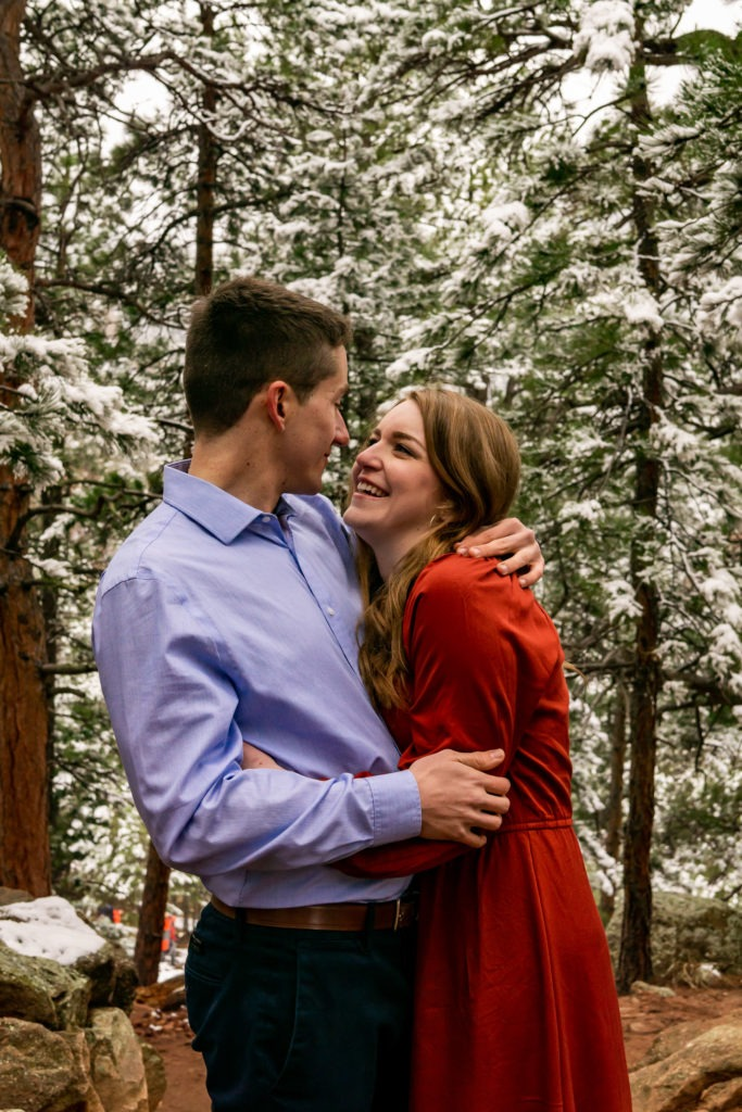 A couple embracing and laughing in a snowy forest during this Boulder engagement session by Gabby Jockers Photography. boulder engagement photography, boulder engagement photos, boulder engagement session, chautauqua park engagement photos, chautauqua park engagement session, chautauqua park photography, Flatirons engagement photos, snowy engagement photos, snowy engagement session, hiking engagement, adventure photos, adventure session, couples photos