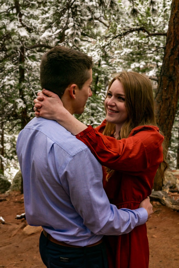 A woman with her hands around the neck of her fiance and smiling into his eyes in a snowy forest during this Boulder engagement session by Gabby Jockers Photography. boulder engagement photography, boulder engagement photos, boulder engagement session, chautauqua park engagement photos, chautauqua park engagement session, chautauqua park photography, Flatirons engagement photos, snowy engagement photos, snowy engagement session, hiking engagement, adventure photos, adventure session, couples photos
