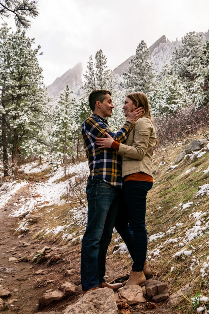 A couple embracing with the man's hand on his fiance's cheek in front of the foggy Flatirons in this Boulder engagement session by Gabby Jockers Photography. boulder engagement photography, boulder engagement photos, boulder engagement session, chautauqua park engagement photos, chautauqua park engagement session, chautauqua park photography, Flatirons engagement photos, snowy engagement photos, snowy engagement session, hiking engagement, adventure photos, adventure session, couples photos