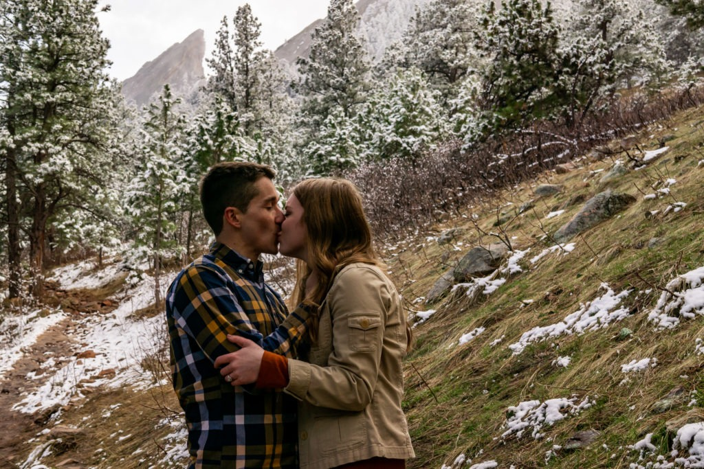 A couple kissing in front of the foggy Flatirons in this Boulder engagement session by Gabby Jockers Photography. boulder engagement photography, boulder engagement photos, boulder engagement session, chautauqua park engagement photos, chautauqua park engagement session, chautauqua park photography, Flatirons engagement photos, snowy engagement photos, snowy engagement session, hiking engagement, adventure photos, adventure session, couples photos