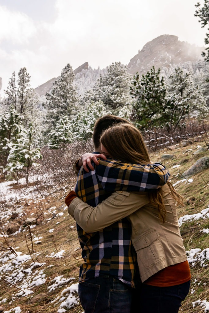 Couple embracing tightly in front of the foggy Flatirons in this Boulder engagement session by Gabby Jockers Photography. boulder engagement photography, boulder engagement photos, boulder engagement session, chautauqua park engagement photos, chautauqua park engagement session, chautauqua park photography, Flatirons engagement photos, snowy engagement photos, snowy engagement session, hiking engagement, adventure photos, adventure session, couples photos