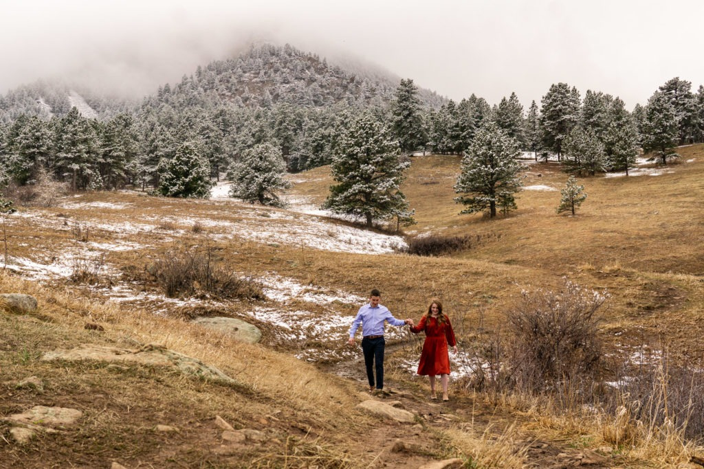 Hand in hand this couple walks down the trail in this Chautauqua Park engagement session by Gabby Jockers Photography. boulder engagement photography, boulder engagement photos, boulder engagement session, chautauqua park engagement photos, chautauqua park engagement session, chautauqua park photography, Flatirons engagement photos, snowy engagement photos, snowy engagement session, hiking engagement, adventure photos, adventure session, couples photos