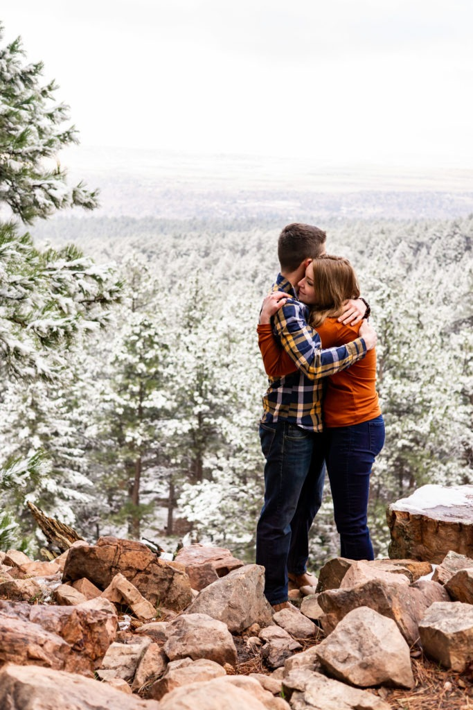 A happy couple giving each other a big hum on a cliff overlooking a snowy forest in this Boulder engagement session by Gabby Jockers Photography. boulder engagement photography, boulder engagement photos, boulder engagement session, chautauqua park engagement photos, chautauqua park engagement session, chautauqua park photography, Flatirons engagement photos, snowy engagement photos, snowy engagement session, hiking engagement, adventure photos, adventure session, couples photos