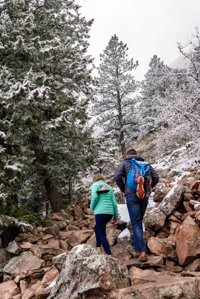 A couple in their puffy jackets walking down a stony, snowy trail in this Boulder engagement session by Gabby Jockers Photography. boulder engagement photography, boulder engagement photos, boulder engagement session, chautauqua park engagement photos, chautauqua park engagement session, chautauqua park photography, Flatirons engagement photos, snowy engagement photos, snowy engagement session, hiking engagement, adventure photos, adventure session, couples photos