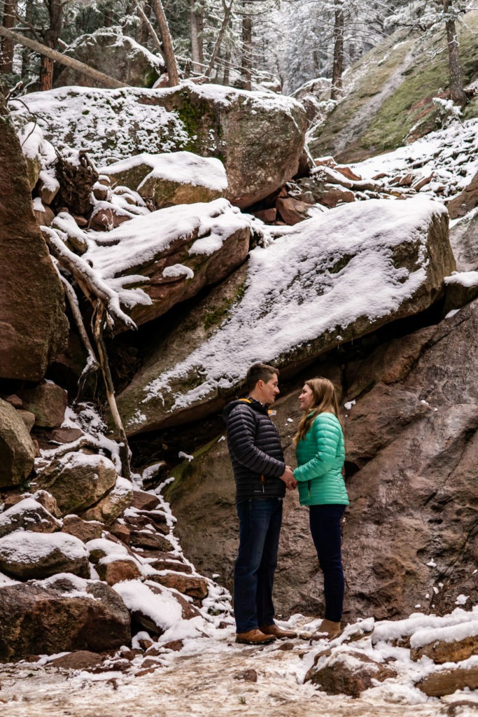 A couple holding hands in their puffies on the trail in this Boulder engagement session by Gabby Jockers Photography. boulder engagement photography, boulder engagement photos, boulder engagement session, chautauqua park engagement photos, chautauqua park engagement session, chautauqua park photography, Flatirons engagement photos, snowy engagement photos, snowy engagement session, hiking engagement, adventure photos, adventure session, couples photos