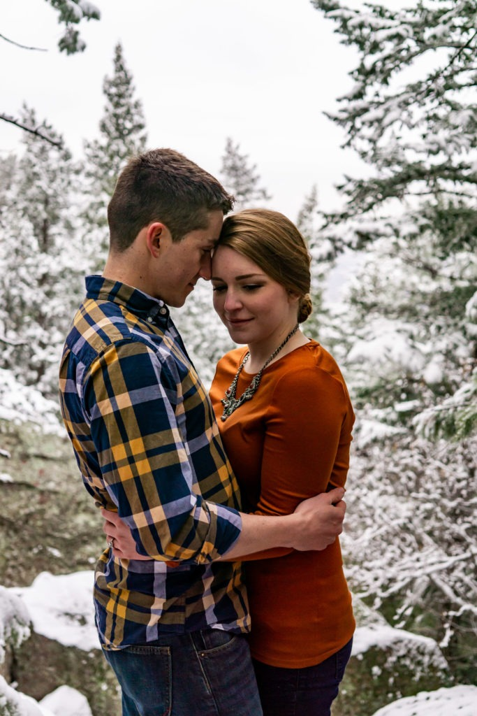 A couple has a quiet moment with foreheads resting together and arms wrapped around each other in this Boulder engagement session by Gabby Jockers Photography. boulder engagement photography, boulder engagement photos, boulder engagement session, chautauqua park engagement photos, chautauqua park engagement session, chautauqua park photography, Flatirons engagement photos, snowy engagement photos, snowy engagement session, hiking engagement, adventure photos, adventure session, couples photos