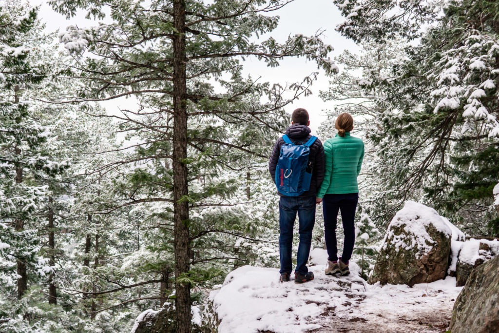 Couples wearing puffies and holding hands on a snowy cliff in this Boulder engagement session. patagonia, engagement photo outfits, engagement session outfits, boulder engagement photography, boulder engagement photos, boulder engagement session, chautauqua park engagement photos, chautauqua park engagement session, chautauqua park photography, Flatirons engagement photos, snowy engagement photos, snowy engagement session, hiking engagement, adventure photos, adventure session, couples photos