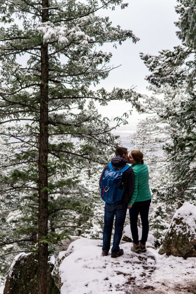 Wearing puffies and kissing on a snowy cliff in this Boulder engagement session. patagonia, kissing engagement photo outfits, engagement session outfits, boulder engagement photography, boulder engagement photos, boulder engagement session, chautauqua park engagement photos, chautauqua park engagement session, chautauqua park photography, Flatirons engagement photos, snowy engagement photos, snowy engagement session, hiking engagement, adventure photos, adventure session, couples photos