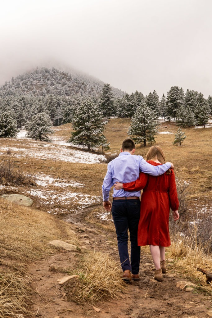 Arm over arm this man and woman walk down the trail in this Chautauqua Park engagement session by Gabby Jockers Photography. boulder engagement photography, boulder engagement photos, boulder engagement session, chautauqua park engagement photos, chautauqua park engagement session, chautauqua park photography, Flatirons engagement photos, snowy engagement photos, snowy engagement session, hiking engagement, adventure photos, adventure session, couples photos