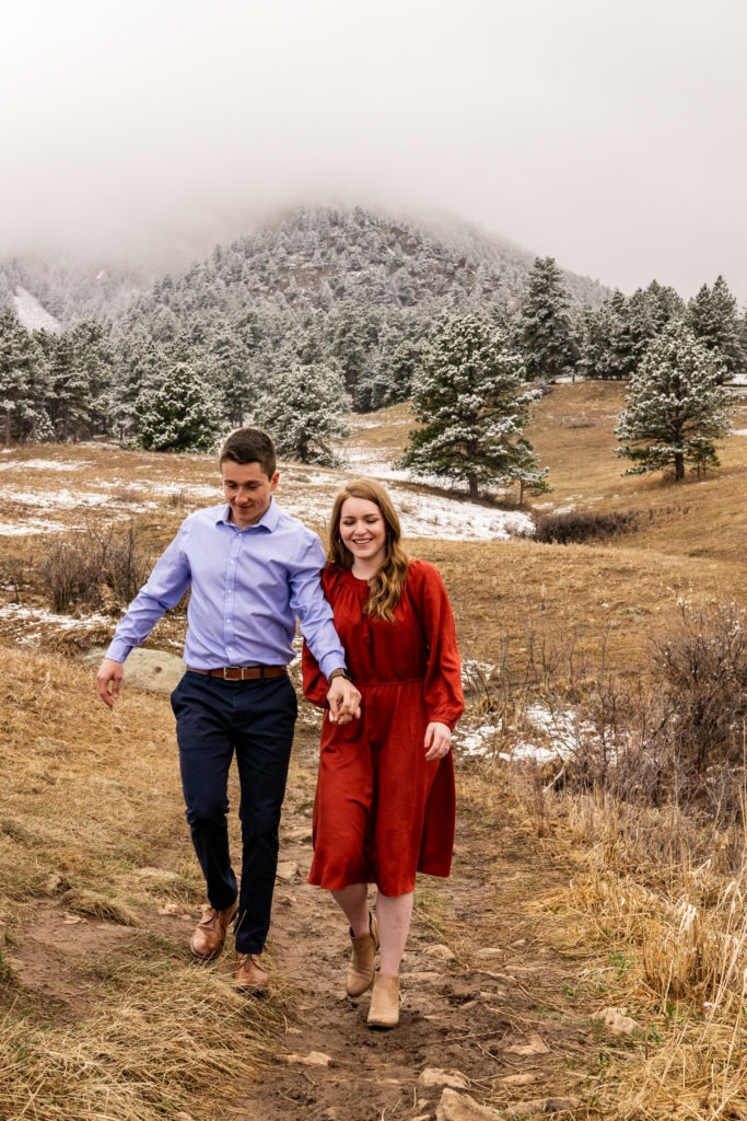 A man and woman happily coming down a trail in this Chautauqua Park engagement session by Gabby Jockers Photography. boulder engagement photography, boulder engagement photos, boulder engagement session, chautauqua park engagement photos, chautauqua park engagement session, chautauqua park photography, Flatirons engagement photos, snowy engagement photos, snowy engagement session, hiking engagement, adventure photos, adventure session, couples photos