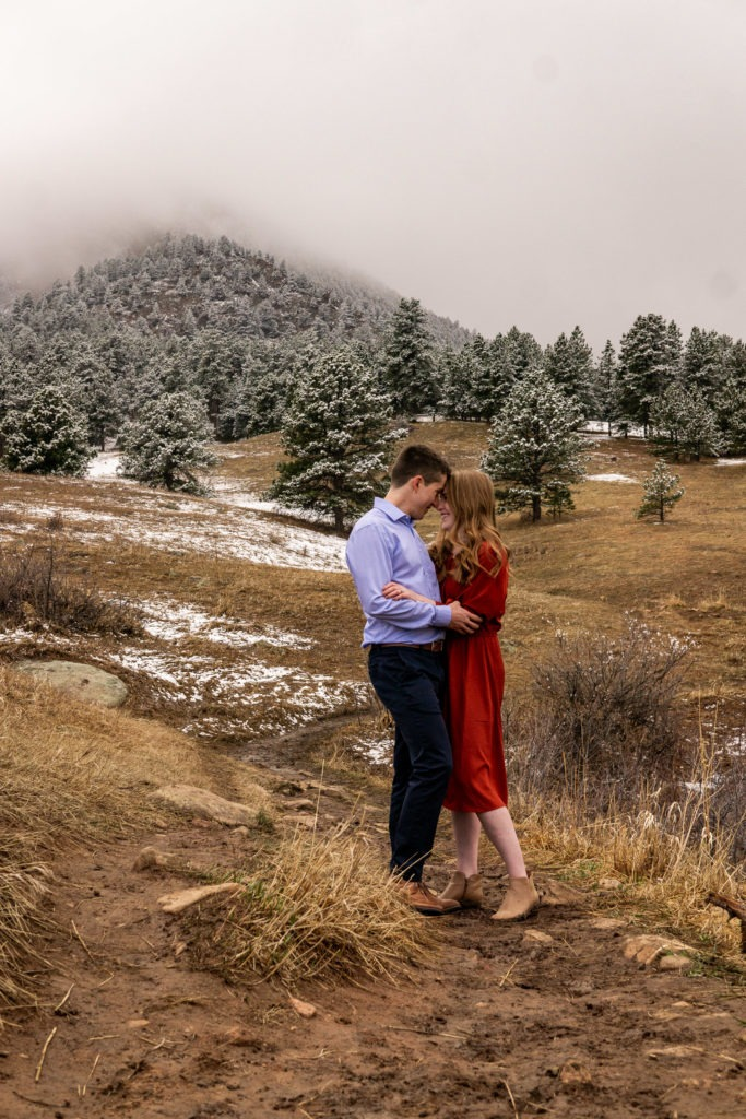 A man in blue and a woman in red embracing in this Chautauqua Park engagement session by Gabby Jockers Photography. boulder engagement photography, boulder engagement photos, boulder engagement session, chautauqua park engagement photos, chautauqua park engagement session, chautauqua park photography, Flatirons engagement photos, snowy engagement photos, snowy engagement session, hiking engagement, adventure photos, adventure session, couples photos