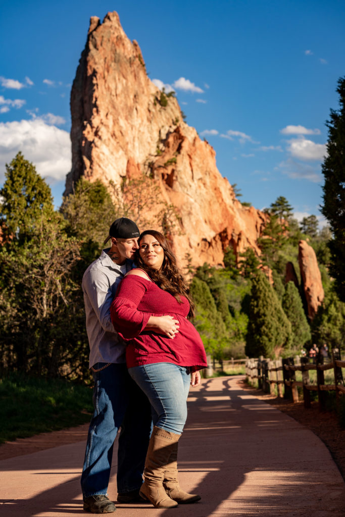 A man and woman embracing in front of red rock formations at Garden of the Gods in Colorado Springs, CO. Photo by Gabby Jockers Photography. Colorado springs engagement photography, Colorado springs engagement photos, colorado springs engagement session, garden of the gods engagement photos, garden of the gods engagement session, garden of the gods photography, garden of the gods wedding, garden of the gods elopement, hiking engagement, adventure photos, adventure session, couples photos