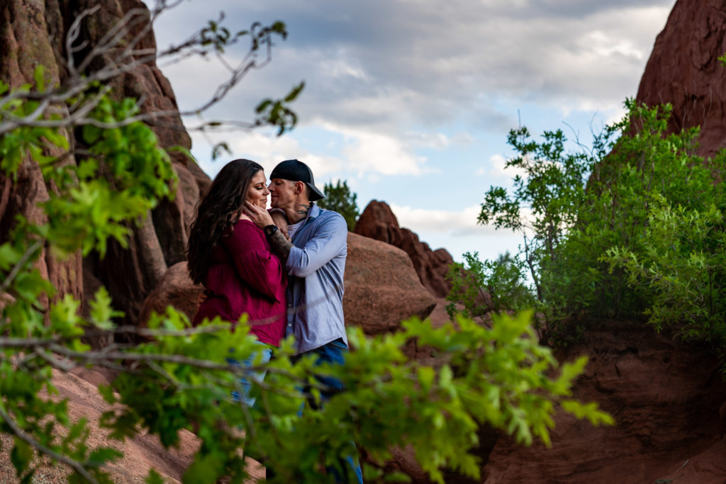 A man and woman hanging out on top of a boulder in front of a red rock wall at Garden of the Gods in Colorado Springs, CO. Photo by Gabby Jockers Photography. Colorado springs engagement photography, Colorado springs engagement photos, colorado springs engagement session, garden of the gods engagement photos, garden of the gods engagement session, garden of the gods photography, garden of the gods wedding, garden of the gods elopement, hiking engagement, adventure photos, adventure session, couples photos