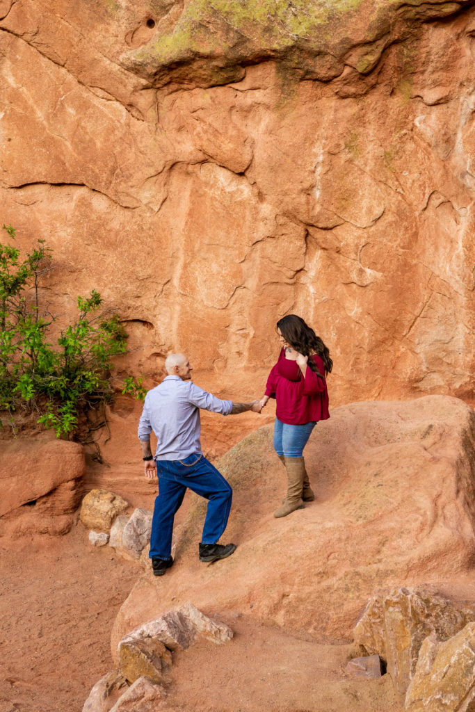 A man and woman hanging out and climbing a boulder in front of a red rock formations at Garden of the Gods in Colorado Springs, CO. Photo by Gabby Jockers Photography. Colorado springs engagement photography, Colorado springs engagement photos, colorado springs engagement session, garden of the gods engagement photos, garden of the gods engagement session, garden of the gods photography, garden of the gods wedding, garden of the gods elopement, hiking engagement, adventure photos, adventure session, couples photos
