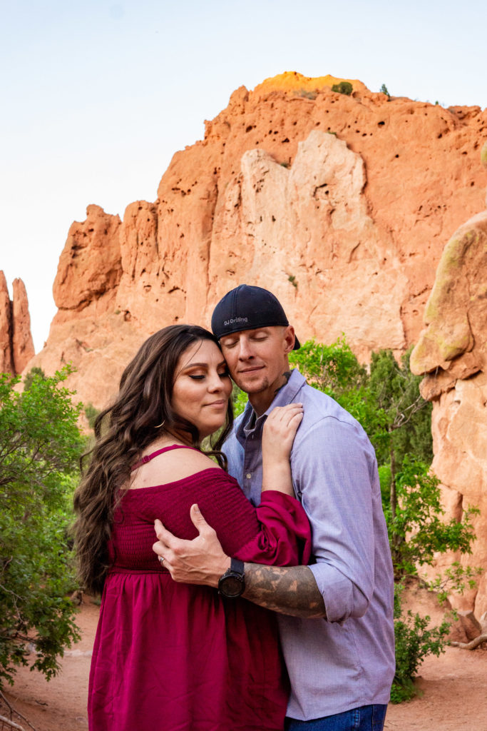 A man and woman hanging out and cuddling each other in front of rock formations at Garden of the Gods in Colorado Springs, CO. Photo by Gabby Jockers Photography. Colorado springs engagement photography, Colorado springs engagement photos, colorado springs engagement session, garden of the gods engagement photos, garden of the gods engagement session, garden of the gods photography, garden of the gods wedding, garden of the gods elopement, hiking engagement, adventure photos, adventure session, couples photos