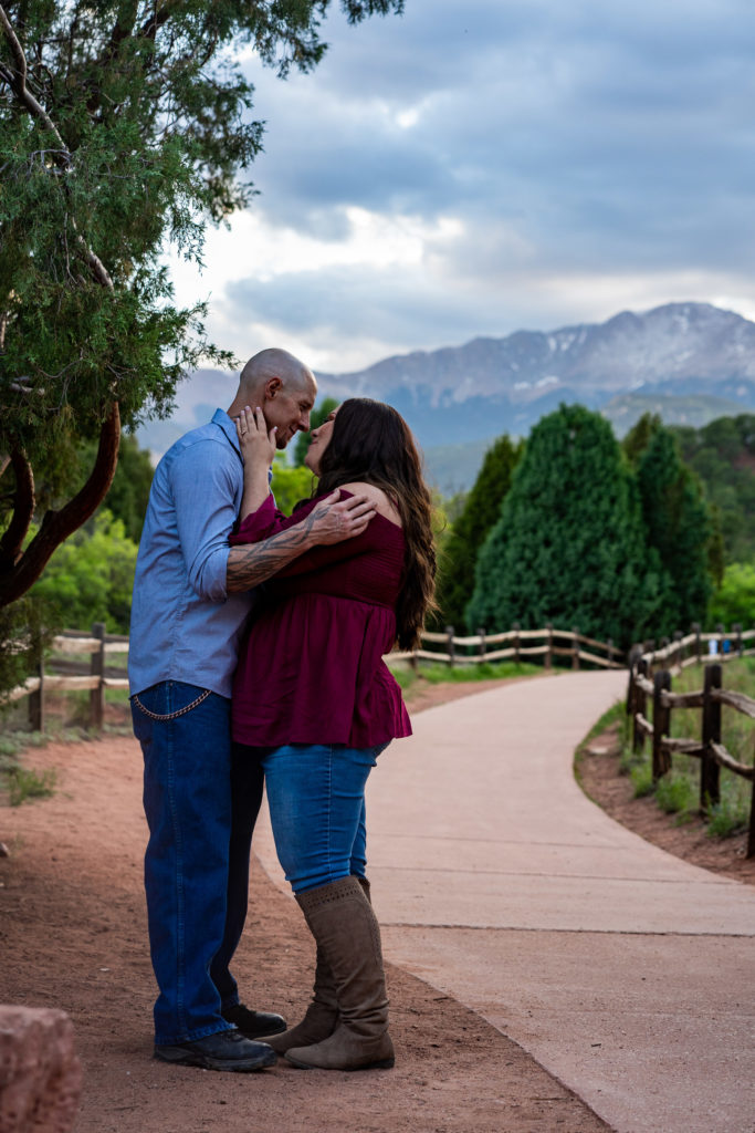 A man and woman holding each other in front of Pike's Peak. Photo by Gabby Jockers Photography. Colorado springs engagement photography, Colorado springs engagement photos, colorado springs engagement session, garden of the gods engagement photos, garden of the gods engagement session, garden of the gods photography, garden of the gods wedding, garden of the gods elopement, hiking engagement, adventure photos, adventure session, couples photos