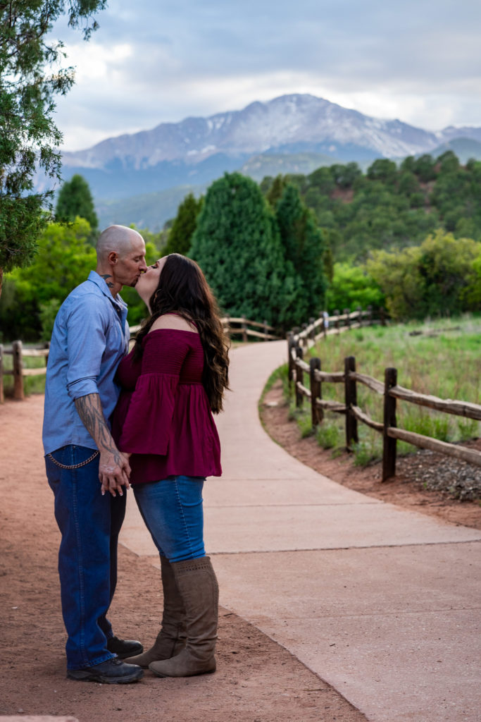 A man and woman kissing while holding hands in front of Pike's Peak. Photo by Gabby Jockers Photography. Colorado springs engagement photography, Colorado springs engagement photos, colorado springs engagement session, garden of the gods engagement photos, garden of the gods engagement session, garden of the gods photography, garden of the gods wedding, garden of the gods elopement, hiking engagement, adventure photos, adventure session, couples photos