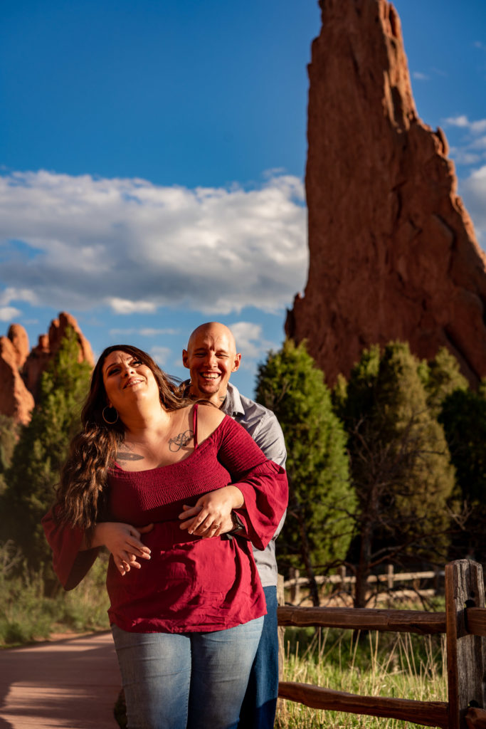 A man and woman laughing in front of red rock formations at Garden of the Gods in Colorado Springs, CO. Photo by Gabby Jockers Photography. Colorado springs engagement photography, Colorado springs engagement photos, colorado springs engagement session, garden of the gods engagement photos, garden of the gods engagement session, garden of the gods photography, garden of the gods wedding, garden of the gods elopement, hiking engagement, adventure photos, adventure session, couples photos
