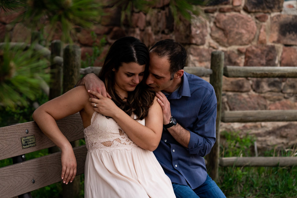 A couple sitting and embracing in a courtyard of a castle ruin in Colorado. Photo by Gabby Jockers Photography. colorado engagement photography, colorado engagement photos, colorado engagement session, mt falcon engagement photos, mt falcon engagement session, denver engagement photography, denver engagement photos, castle engagement photos, sunset engagement session, hiking engagement, adventure photos, adventure session, couples photos, blue hour photos