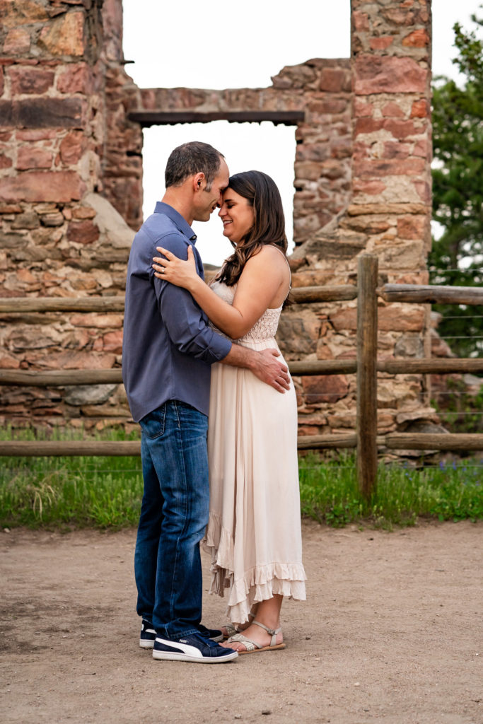 A couple kissing in front of a bright gold sun outside at the Mount Falcon castle in Colorado. Photo by Gabby Jockers Photography. colorado engagement photography, colorado engagement photos, colorado engagement session, mt falcon engagement photos, mt falcon engagement session, denver engagement photography, denver engagement photos, castle engagement photos, sunset engagement session, hiking engagement, adventure photos, adventure session, couples photos, blue hour photos