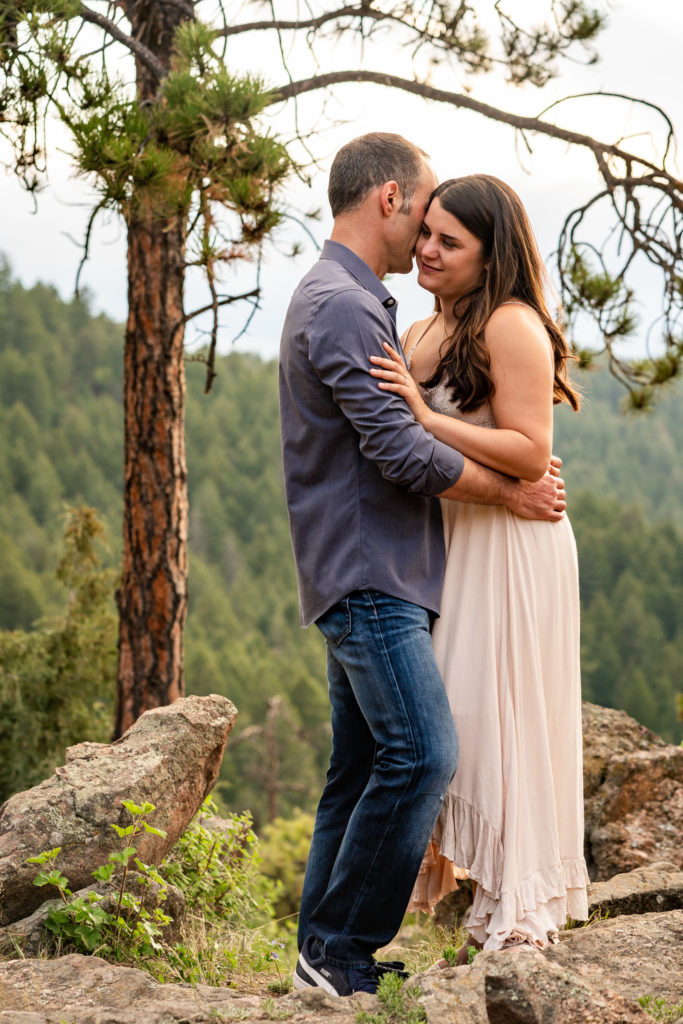 A man and woman embracing under a beautiful tree in front of a tree-lined hill in Colorado. Photo by Gabby Jockers Photography. colorado engagement photography, colorado engagement photos, colorado engagement session, mt falcon engagement photos, mt falcon engagement session, denver engagement photography, denver engagement photos, castle engagement photos, sunset engagement session, hiking engagement, adventure photos, adventure session, couples photos, blue hour photos