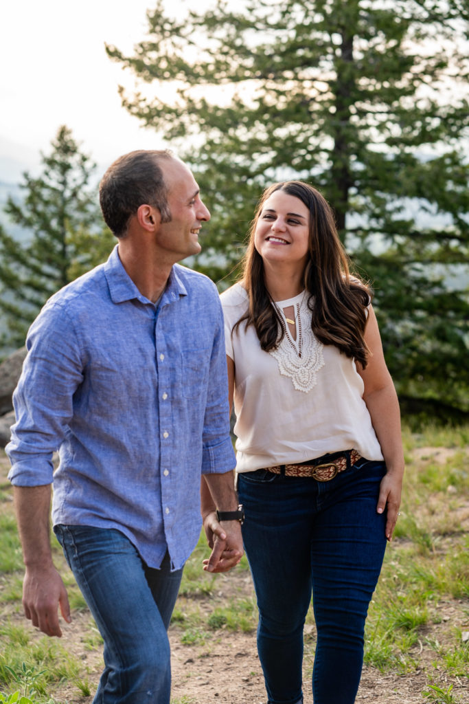A man and woman walking over a rocky trail and holding hands outside in Colorado. Photo by Gabby Jockers Photography. colorado engagement photography, colorado engagement photos, colorado engagement session, mt falcon engagement photos, mt falcon engagement session, denver engagement photography, denver engagement photos, castle engagement photos, sunset engagement session, hiking engagement, adventure photos, adventure session, couples photos, blue hour photos