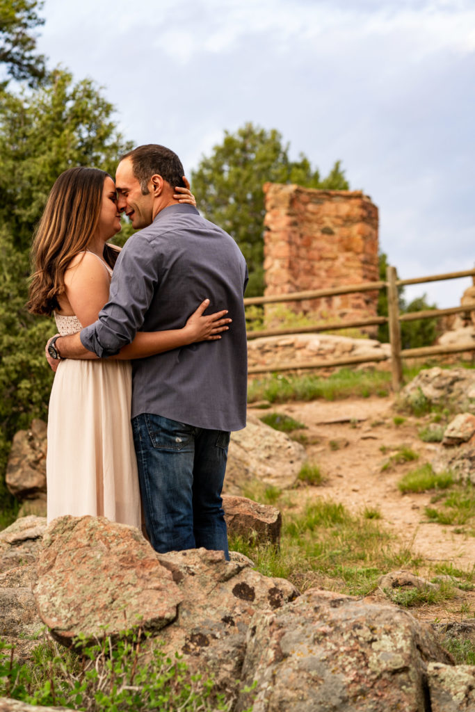 A couple embracing in front of castle ruins in Colorado. Photo by Gabby Jockers Photography. colorado engagement photography, colorado engagement photos, colorado engagement session, mt falcon engagement photos, mt falcon engagement session, denver engagement photography, denver engagement photos, castle engagement photos, sunset engagement session, hiking engagement, adventure photos, adventure session, couples photos, blue hour photos
