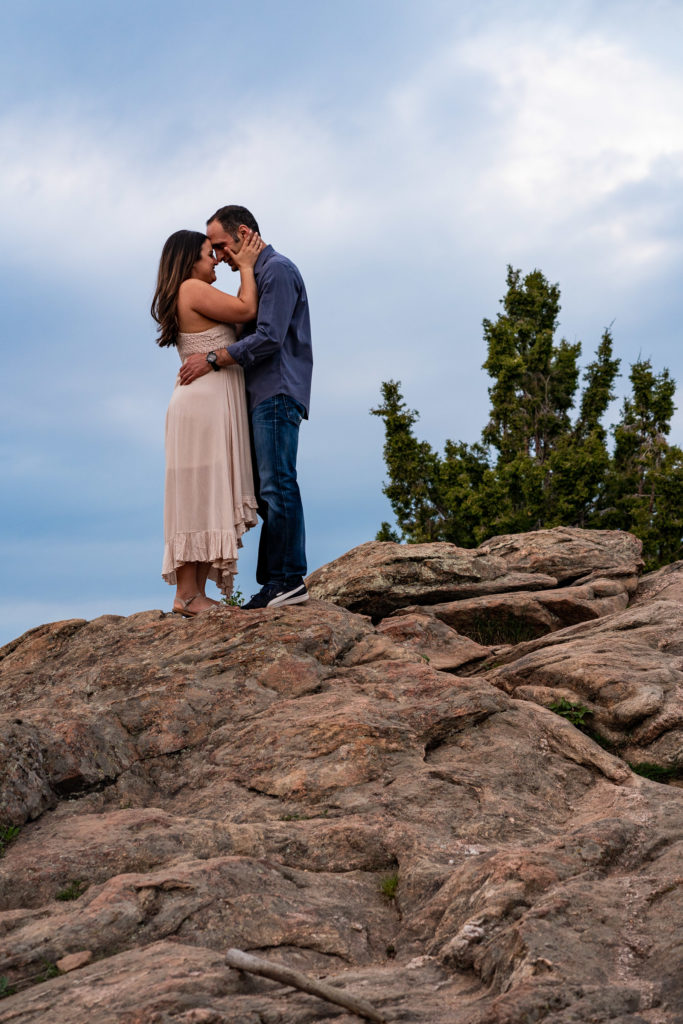 A man and woman embracing on top of a boulder in front of a deep blue sky in Colorado. Photo by Gabby Jockers Photography. colorado engagement photography, colorado engagement photos, colorado engagement session, mt falcon engagement photos, mt falcon engagement session, denver engagement photography, denver engagement photos, castle engagement photos, sunset engagement session, hiking engagement, adventure photos, adventure session, couples photos, blue hour photos