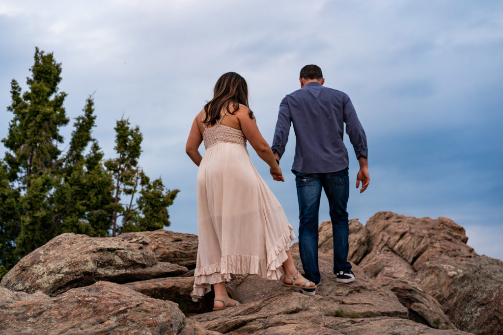 A couple climbs up a boulder in front of deep blue skies in Colorado. Photo by Gabby Jockers Photography. colorado engagement photography, colorado engagement photos, colorado engagement session, mt falcon engagement photos, mt falcon engagement session, denver engagement photography, denver engagement photos, castle engagement photos, sunset engagement session, hiking engagement, adventure photos, adventure session, couples photos, blue hour photos