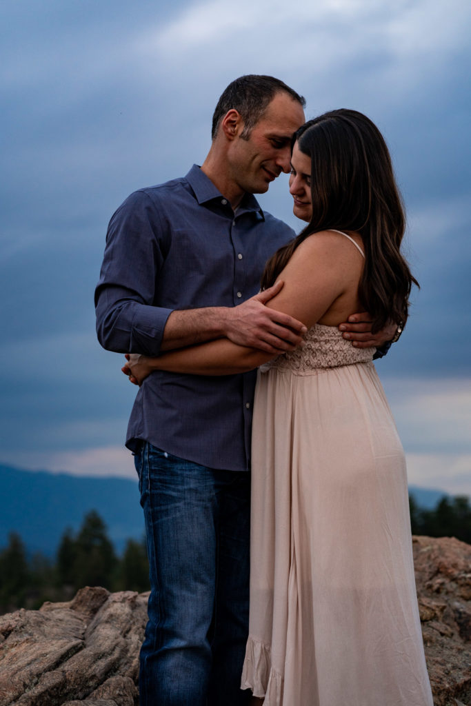 A man and woman wrapped up in each others arms on a boulder in front of deep blue skies in Colorado. Photo by Gabby Jockers Photography. colorado engagement photography, colorado engagement photos, colorado engagement session, mt falcon engagement photos, mt falcon engagement session, denver engagement photography, denver engagement photos, castle engagement photos, sunset engagement session, hiking engagement, adventure photos, adventure session, couples photos, blue hour photos