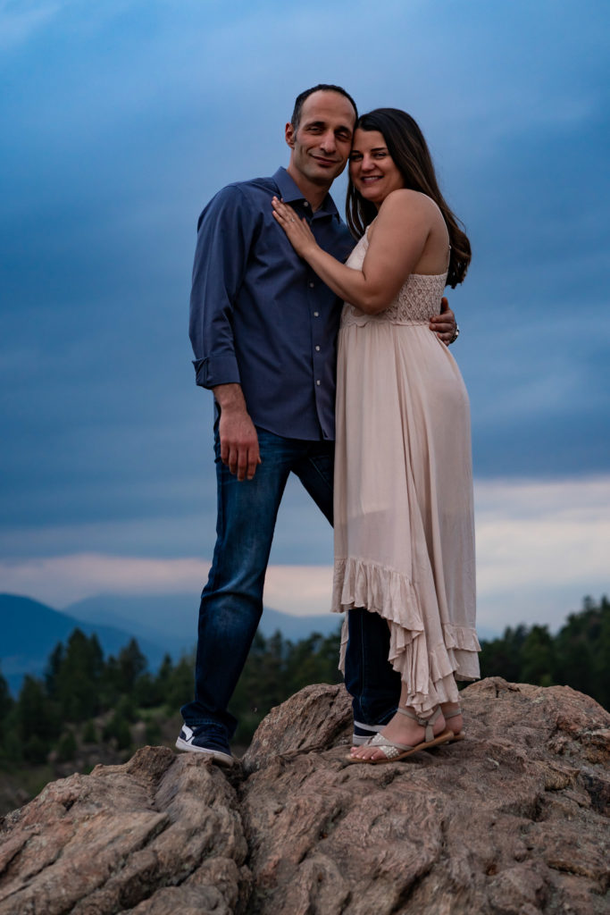 A man and woman wrapped up in each others arms and smiling at the camera on a boulder in front of a sunset in Colorado. Photo by Gabby Jockers Photography. colorado engagement photography, colorado engagement photos, colorado engagement session, mt falcon engagement photos, mt falcon engagement session, denver engagement photography, denver engagement photos, castle engagement photos, sunset engagement session, hiking engagement, adventure photos, adventure session, couples photos, blue hour photos