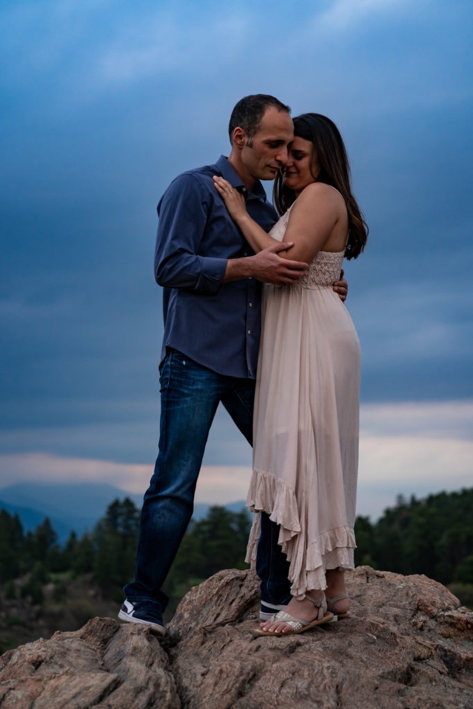 A man and woman wrapped up in each others arms on a boulder in front of a sunset in Colorado. Photo by Gabby Jockers Photography. colorado engagement photography, colorado engagement photos, colorado engagement session, mt falcon engagement photos, mt falcon engagement session, denver engagement photography, denver engagement photos, castle engagement photos, sunset engagement session, hiking engagement, adventure photos, adventure session, couples photos, blue hour photos