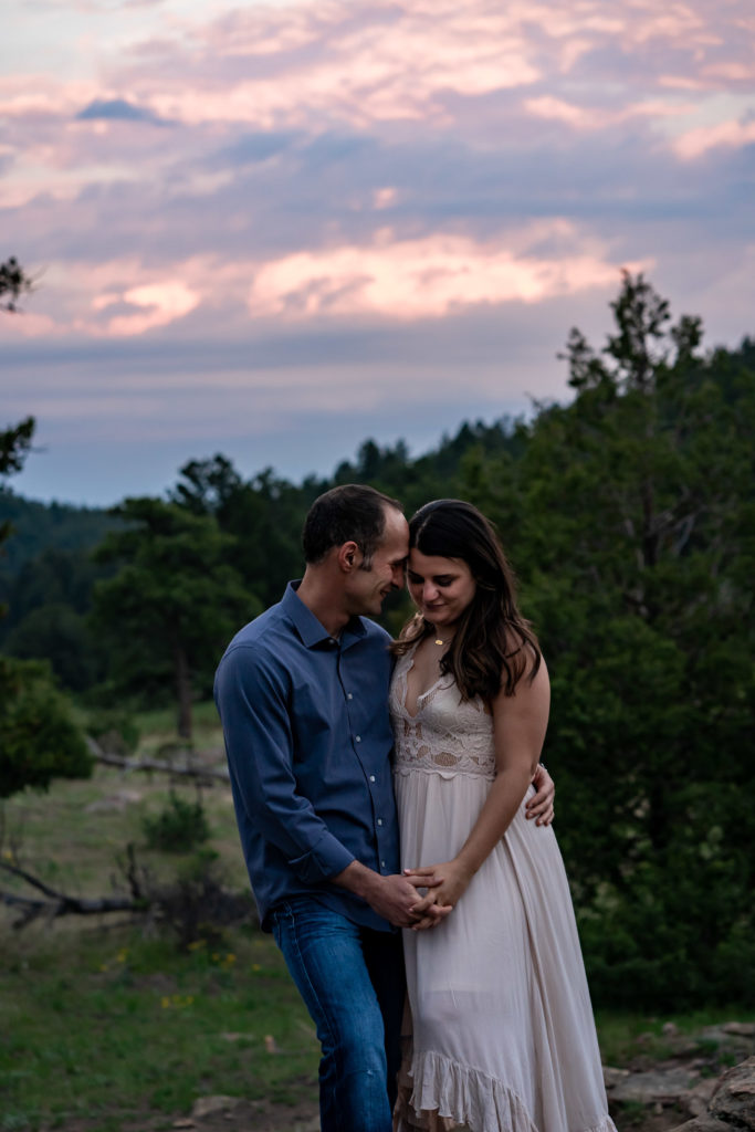 A man and woman wrapped up in each others arms in front of a sunset in Colorado. Photo by Gabby Jockers Photography. colorado engagement photography, colorado engagement photos, colorado engagement session, mt falcon engagement photos, mt falcon engagement session, denver engagement photography, denver engagement photos, castle engagement photos, sunset engagement session, hiking engagement, adventure photos, adventure session, couples photos, blue hour photos