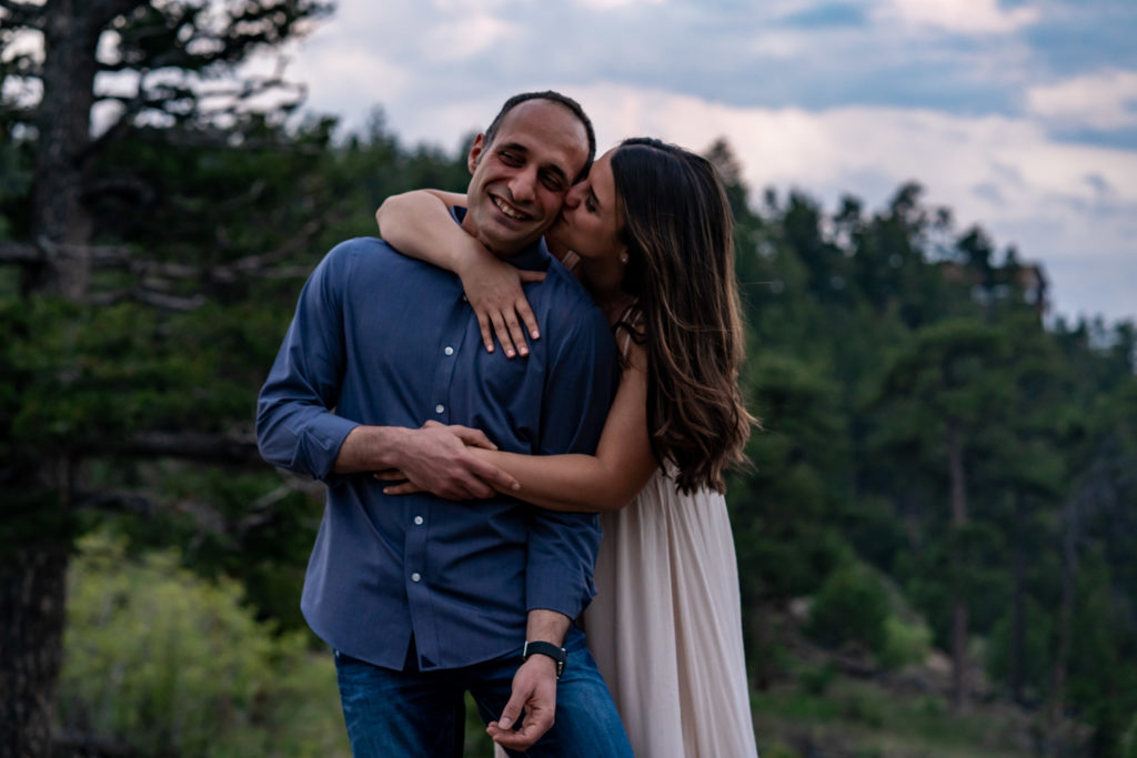 A woman wrapping her arms around her fiance to give him a kiss. Photo by Gabby Jockers Photography. colorado engagement photography, colorado engagement photos, colorado engagement session, mt falcon engagement photos, mt falcon engagement session, denver engagement photography, denver engagement photos, castle engagement photos, sunset engagement session, hiking engagement, adventure photos, adventure session, couples photos, blue hour photos