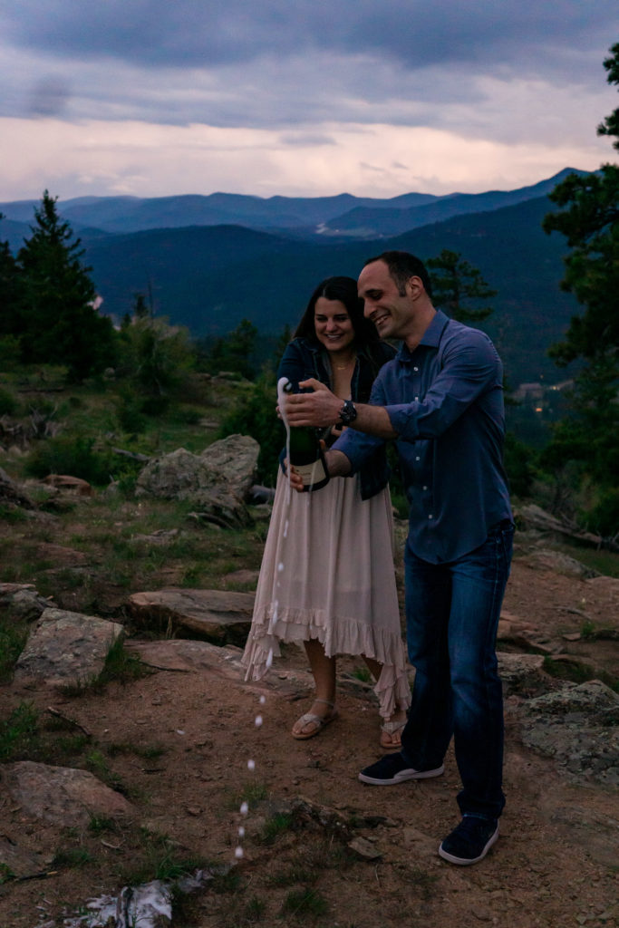 A man and woman celebrating their engagement by popping a bottle of champagne in front of a mountain sunset. Photo by Gabby Jockers Photography. colorado engagement photography, colorado engagement photos, colorado engagement session, mt falcon engagement photos, mt falcon engagement session, denver engagement photography, denver engagement photos, castle engagement photos, sunset engagement session, hiking engagement, adventure photos, adventure session, couples photos, blue hour photos