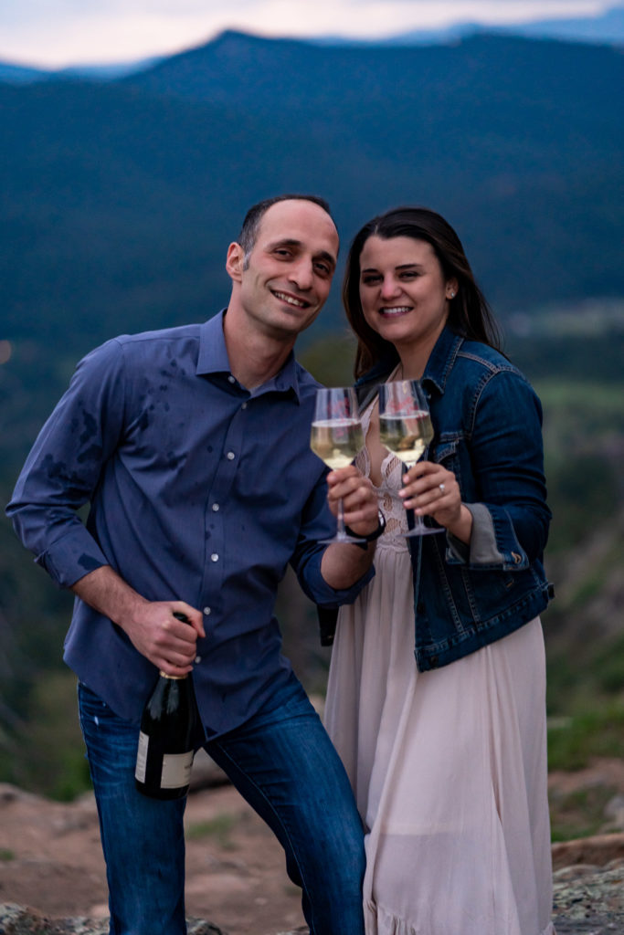A man and women holding two wine glasses of champagne and smiling. Photo by Gabby Jockers Photography. colorado engagement photography, colorado engagement photos, colorado engagement session, mt falcon engagement photos, mt falcon engagement session, denver engagement photography, denver engagement photos, castle engagement photos, sunset engagement session, hiking engagement, adventure photos, adventure session, couples photos, blue hour photos
