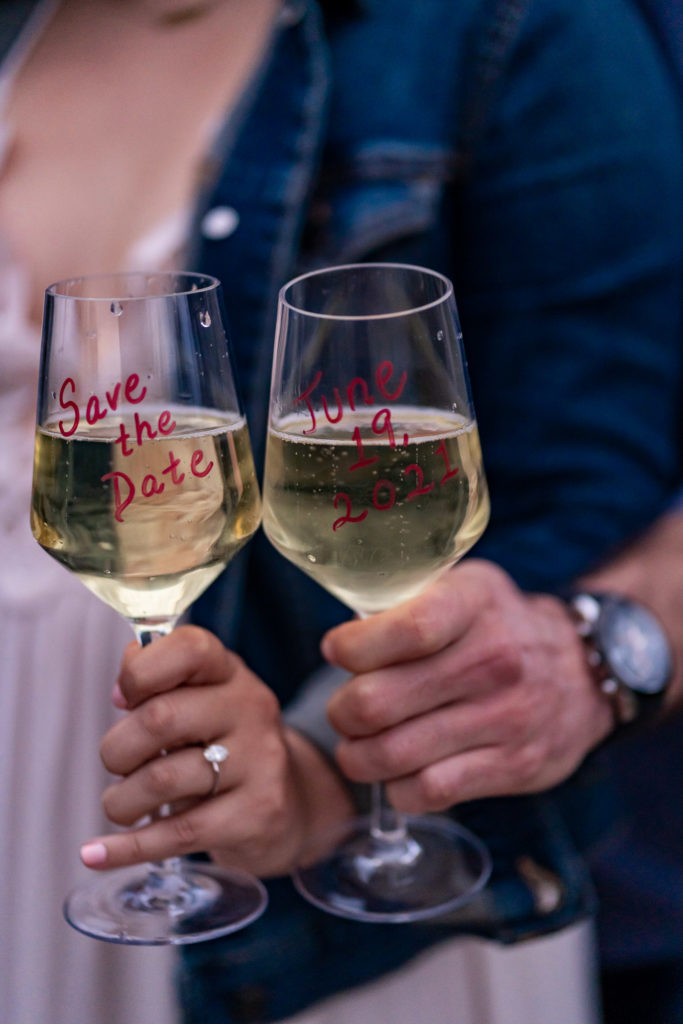 A couple's hand's holding two glasses of champagne with a wedding save the date written on the glasses. Photo by Gabby Jockers Photography. colorado engagement photography, colorado engagement photos, colorado engagement session, mt falcon engagement photos, mt falcon engagement session, denver engagement photography, denver engagement photos, castle engagement photos, sunset engagement session, hiking engagement, adventure photos, adventure session, couples photos, blue hour photos