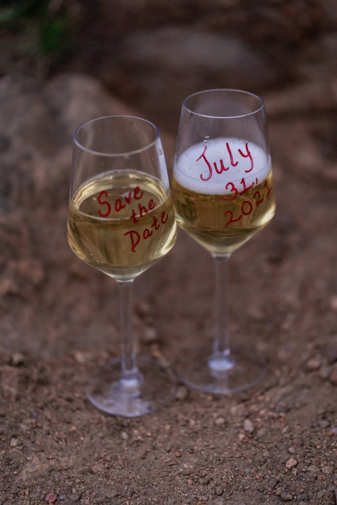 Two glasses of champagne with a wedding save the date written on the glasses. Photo by Gabby Jockers Photography. colorado engagement photography, colorado engagement photos, colorado engagement session, mt falcon engagement photos, mt falcon engagement session, denver engagement photography, denver engagement photos, castle engagement photos, sunset engagement session, hiking engagement, adventure photos, adventure session, couples photos, blue hour photos