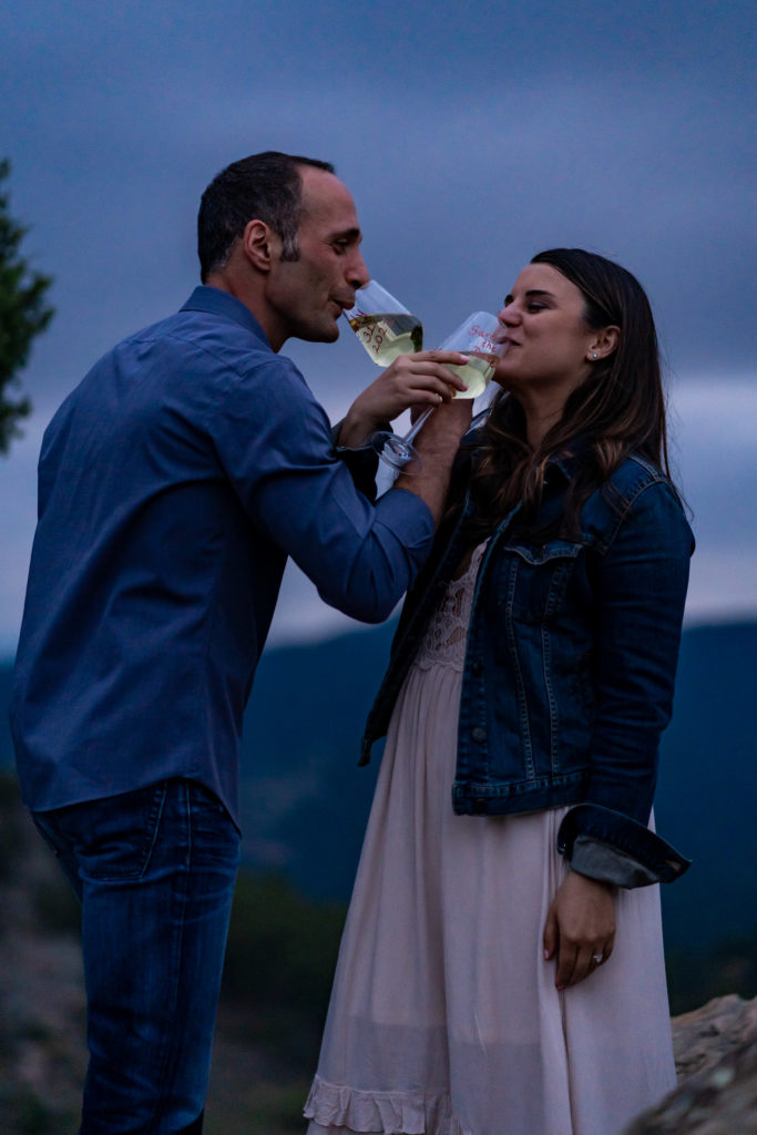 In the darkness after the sun set, this cute couple cheered with some champagne! Photo by Gabby Jockers Photography. colorado engagement photography, colorado engagement photos, colorado engagement session, mt falcon engagement photos, mt falcon engagement session, denver engagement photography, denver engagement photos, castle engagement photos, sunset engagement session, hiking engagement, adventure photos, adventure session, couples photos, blue hour photos