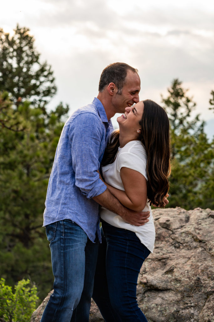 A man holding on to his fiance and making her laugh in front of a sunny sky in Colorado. Photo by Gabby Jockers Photography. colorado engagement photography, colorado engagement photos, colorado engagement session, mt falcon engagement photos, mt falcon engagement session, denver engagement photography, denver engagement photos, castle engagement photos, sunset engagement session, hiking engagement, adventure photos, adventure session, couples photos, blue hour photos