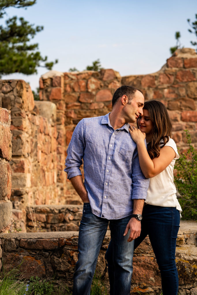 A man and woman in a quiet embrace in front of a crumbling brick wall in Colorado. Photo by Gabby Jockers Photography. colorado engagement photography, colorado engagement photos, colorado engagement session, mt falcon engagement photos, mt falcon engagement session, denver engagement photography, denver engagement photos, castle engagement photos, sunset engagement session, hiking engagement, adventure photos, adventure session, couples photos, blue hour photos