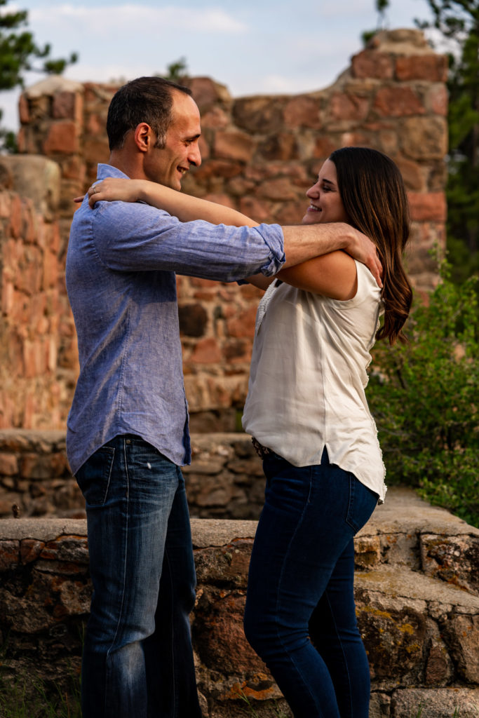 A couple giving each other shoulder massages in front of a crumbling brick wall. Photo by Gabby Jockers Photography. colorado engagement photography, colorado engagement photos, colorado engagement session, mt falcon engagement photos, mt falcon engagement session, denver engagement photography, denver engagement photos, castle engagement photos, sunset engagement session, hiking engagement, adventure photos, adventure session, couples photos, blue hour photos