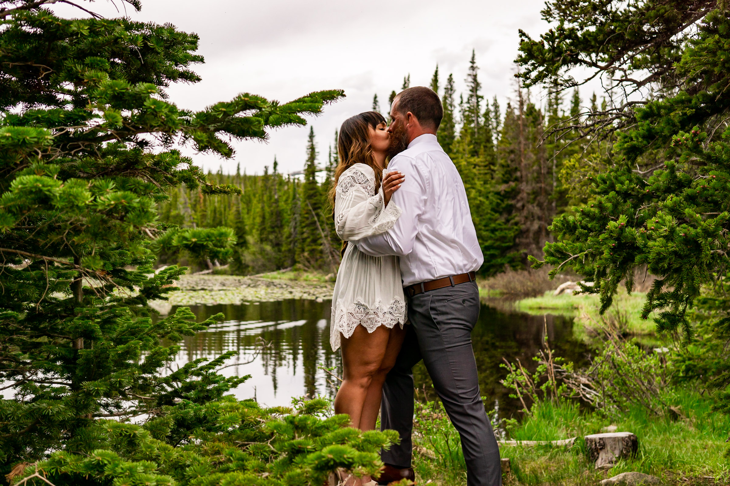 A man and woman kissing in front of a lake in the woods in Colorado. Photo by Gabby Jockers Photography. brainard lake engagement photography, brainard lake engagement photos, brainard lake engagement session, colorado engagement photos, colorado engagement session, colorado photography, mountain, engagement photos, sunset engagement session, hiking engagement, adventure photos, adventure session, couples photos, blue hour photos