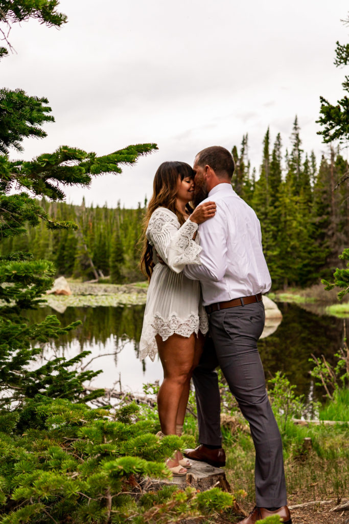 A man and woman in a quiet and happy embrace in front of a lake in the woods. Photo by Gabby Jockers Photography. brainard lake engagement photography, brainard lake engagement photos, brainard lake engagement session, colorado engagement photos, colorado engagement session, colorado photography, mountain, engagement photos, sunset engagement session, hiking engagement, adventure photos, adventure session, couples photos, blue hour photos