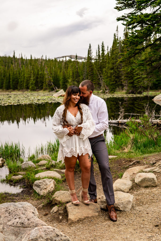 A man and woman holding on to each other and snuggling in front of a lake. Photo by Gabby Jockers Photography. brainard lake engagement photography, brainard lake engagement photos, brainard lake engagement session, colorado engagement photos, colorado engagement session, colorado photography, mountain, engagement photos, sunset engagement session, hiking engagement, adventure photos, adventure session, couples photos, blue hour photos