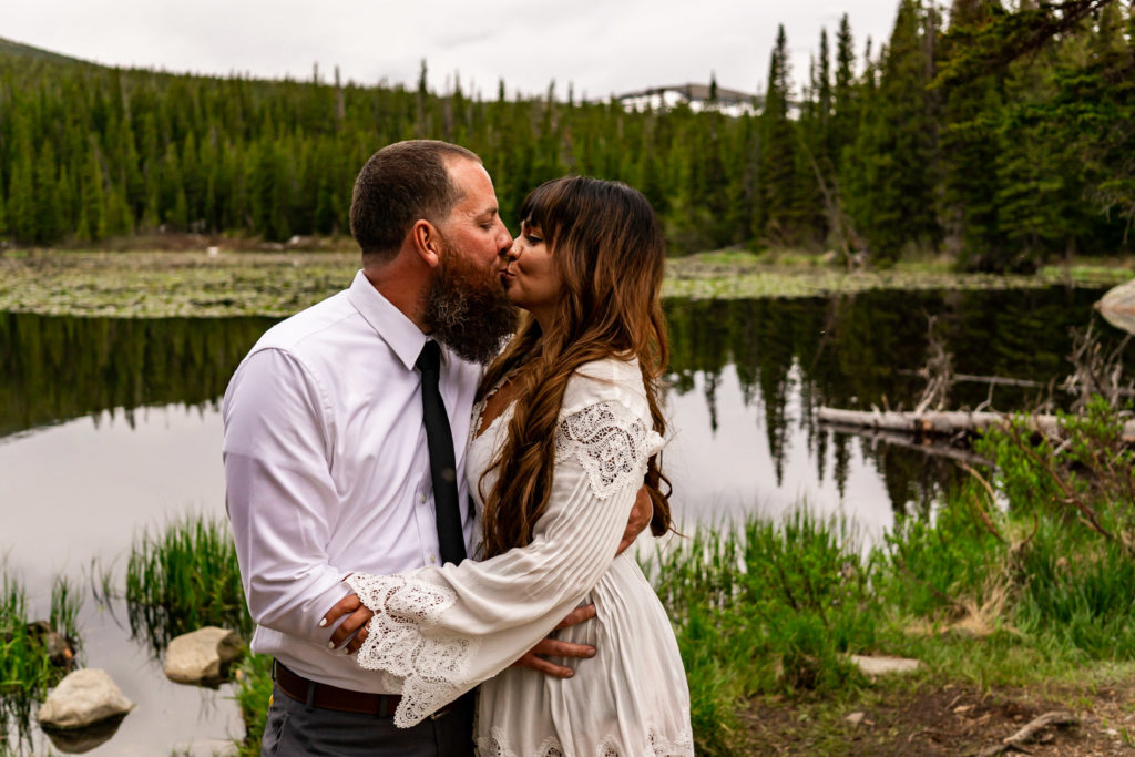 A man and woman holding on to each other and kissing in front of a lake. Photo by Gabby Jockers Photography. brainard lake engagement photography, brainard lake engagement photos, brainard lake engagement session, colorado engagement photos, colorado engagement session, colorado photography, mountain, engagement photos, sunset engagement session, hiking engagement, adventure photos, adventure session, couples photos, blue hour photos