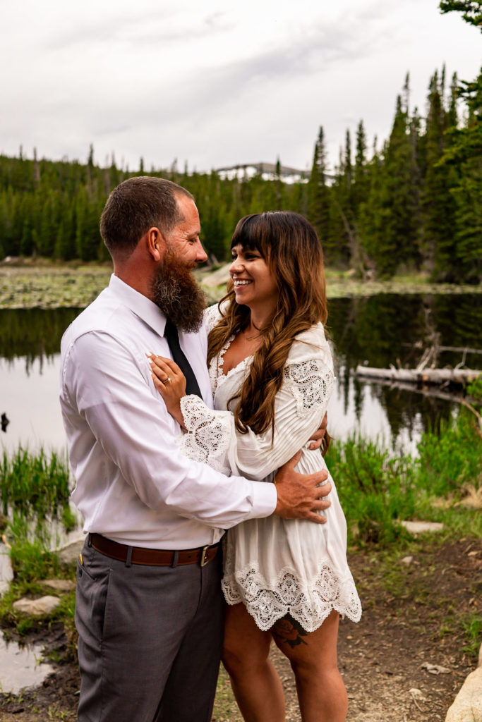 A man and woman holding on to each other and laughing. Photo by Gabby Jockers Photography. brainard lake engagement photography, brainard lake engagement photos, brainard lake engagement session, colorado engagement photos, colorado engagement session, colorado photography, mountain, engagement photos, sunset engagement session, hiking engagement, adventure photos, adventure session, couples photos, blue hour photos